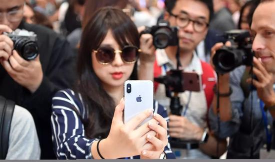 一位正在试用iPhone X的女记者。@视觉中国